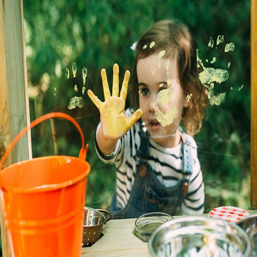 little girl playing with mud pie kitchen